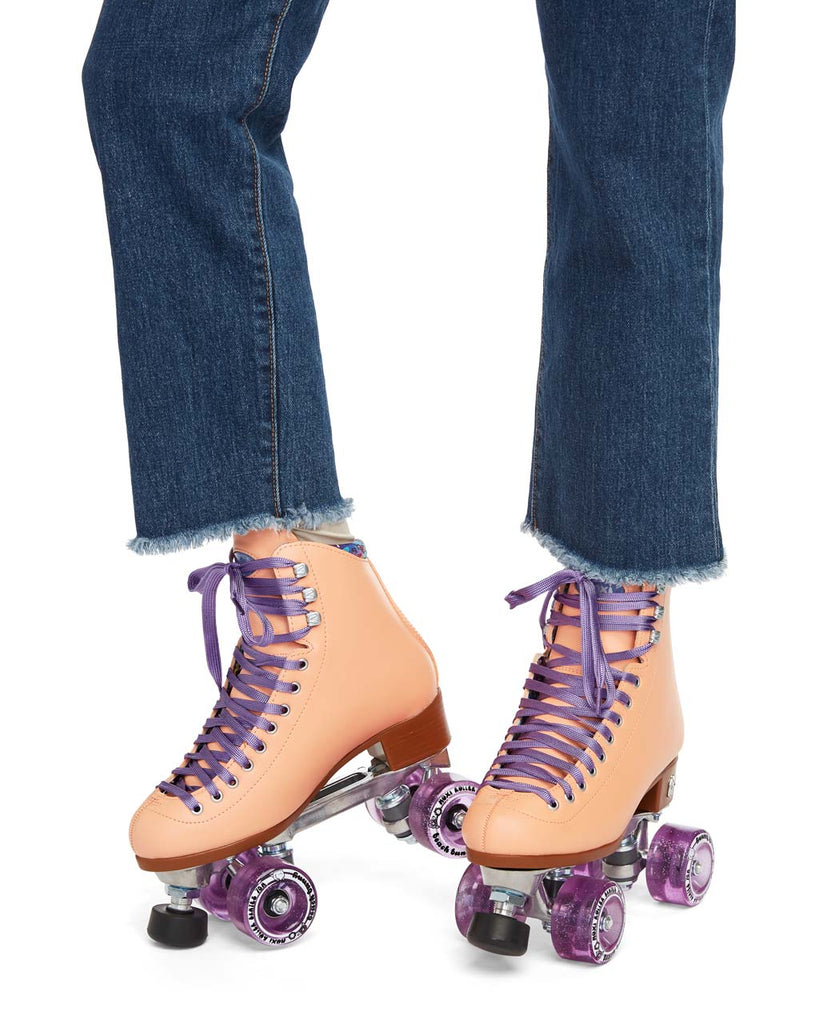 These peach-colored roller-skates feature purple laces and sparkly purple wheels.