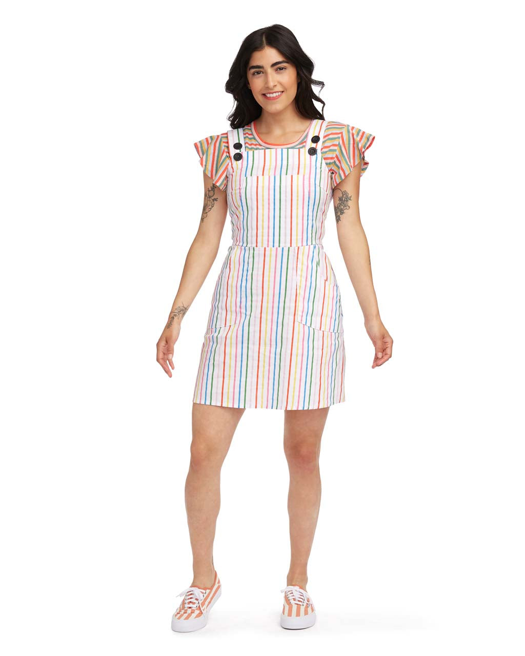 woman wearing the rainbow stripe overall dress with striped sneakers