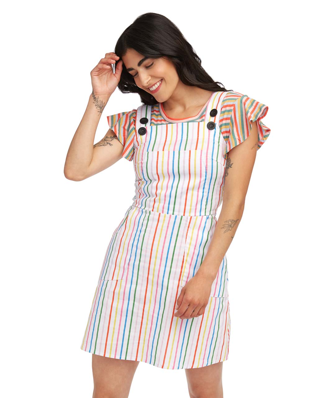 woman wearing a striped tee and rainbow striped overall dress