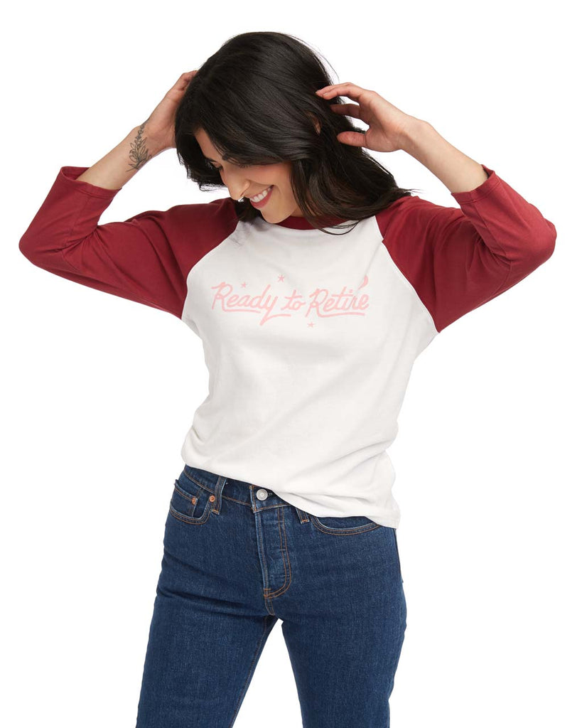 "Woman in a white baseball tee with red 3/4 length sleeves and a pink ""Ready to Retire"" graphic."