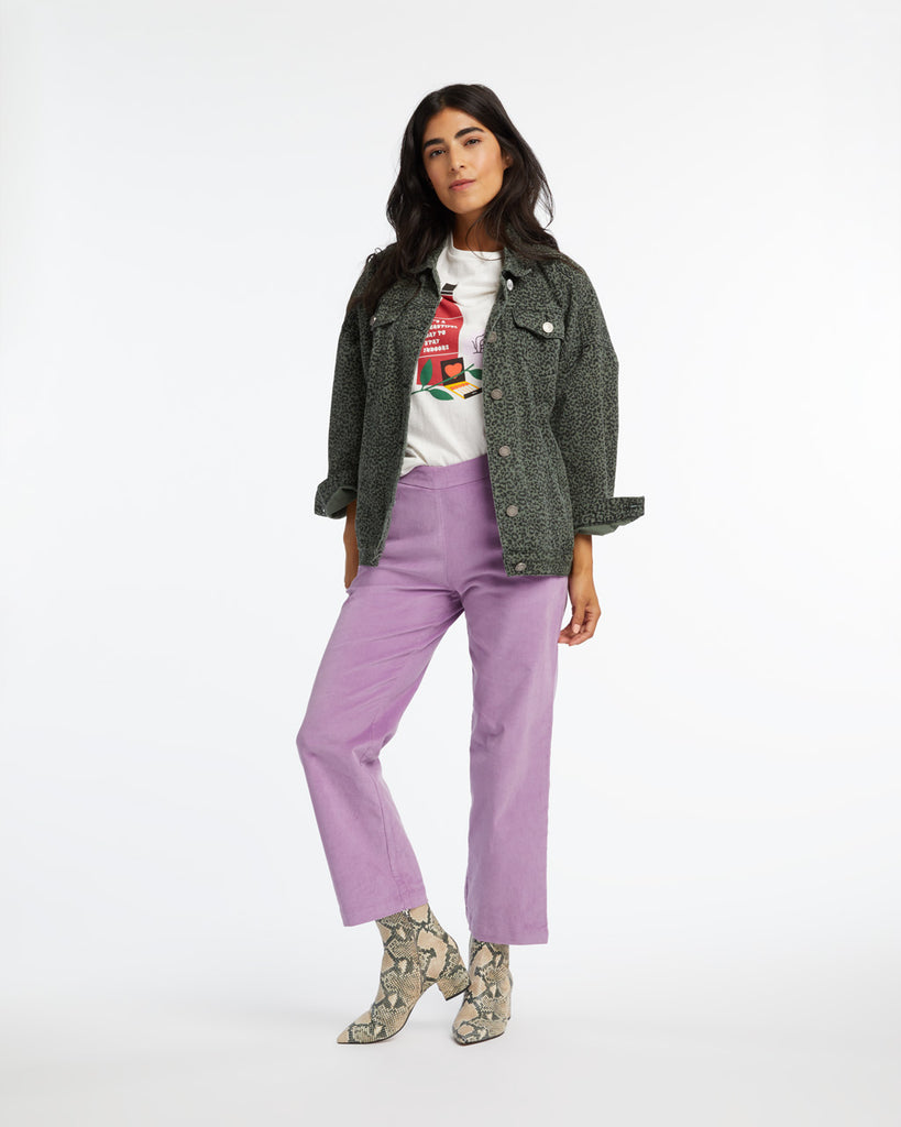 woman wearing purple corduroy pants with an animal print jacket, graphic tee, and snakeskin boots