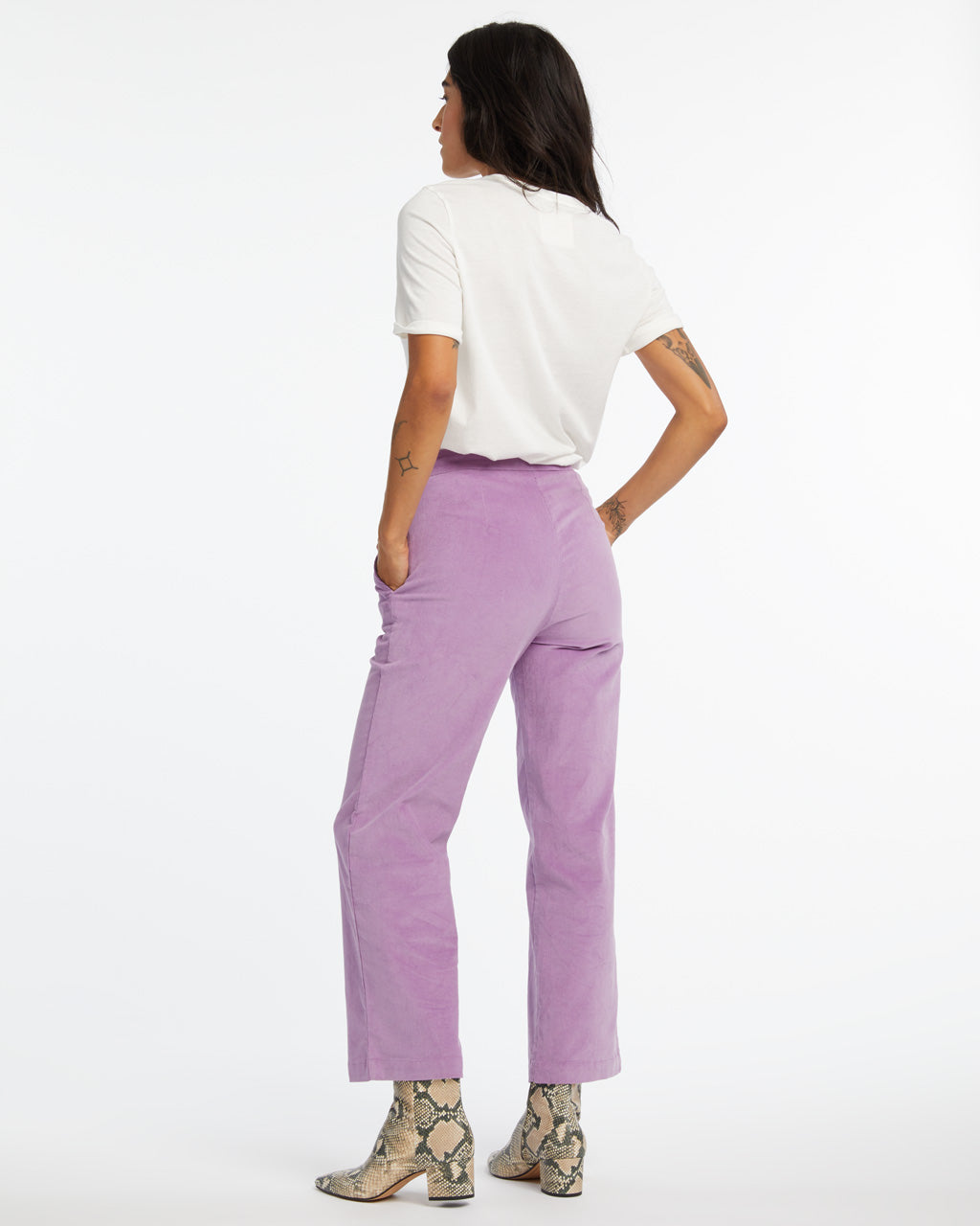 back view of woman wearing purple corduroy pants with a t-shirt and snakeskin boots