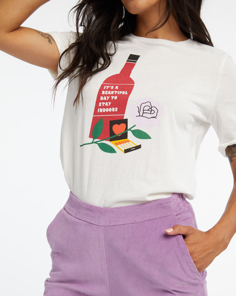 Woman in a white midi sleeve tshirt with a still life graphic in the center.