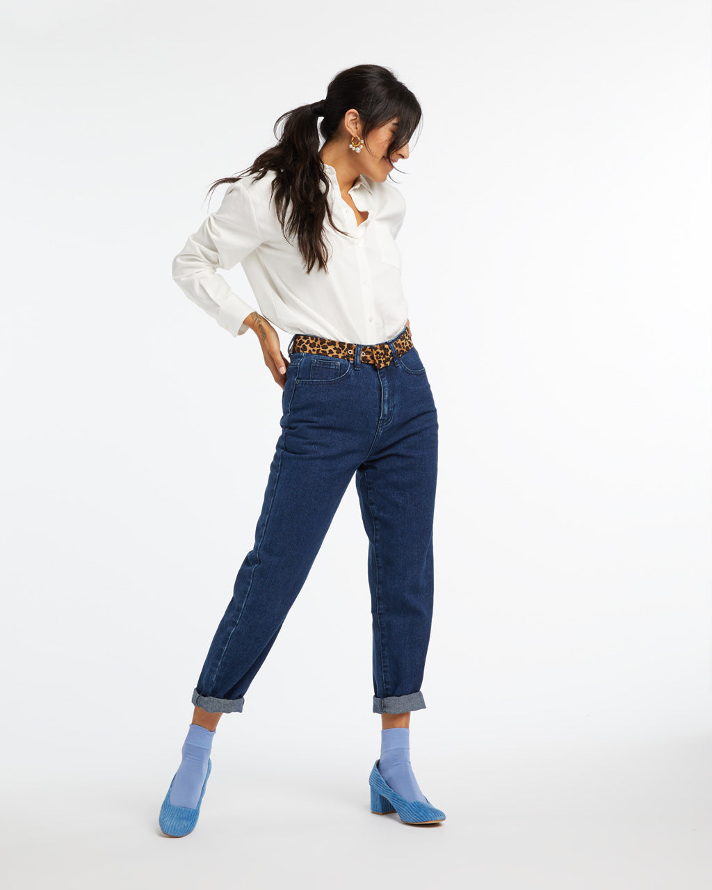 Indigo mom jeans styled with a white buttondown and blue heels.