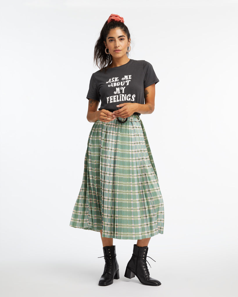 Woman in a graphic tshirt, black boots, and a green plaid skirt with attached belt.