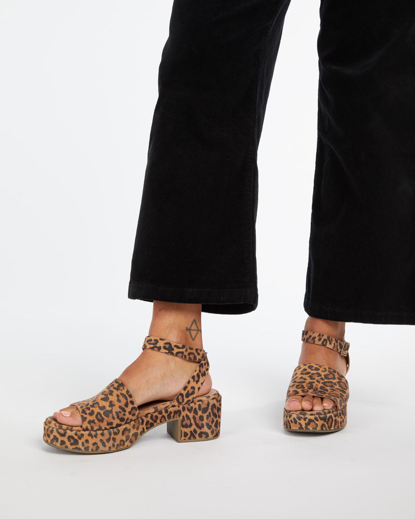 Cropped in shot of leopard platform sandals with 2.5 inch heel.