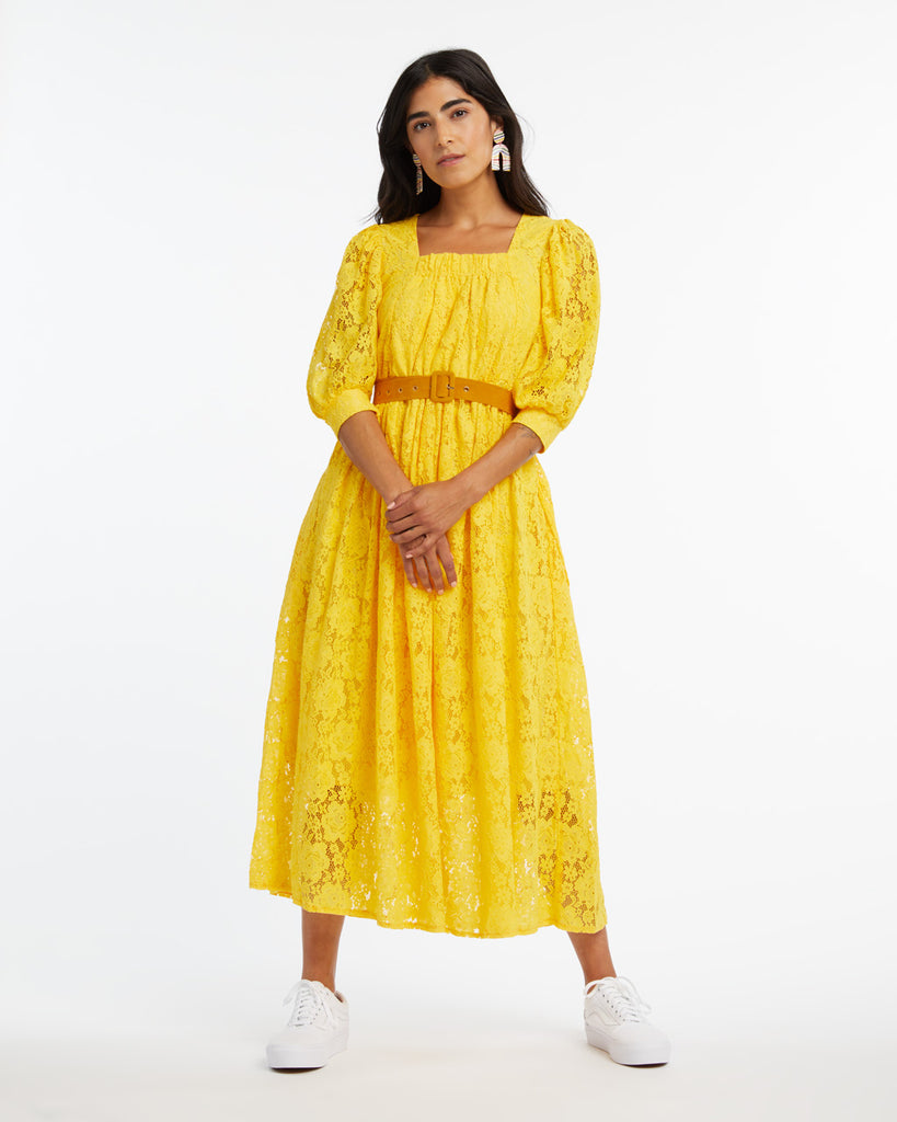 Woman in a midi length yellow lace dress with cropped puff sleeves.