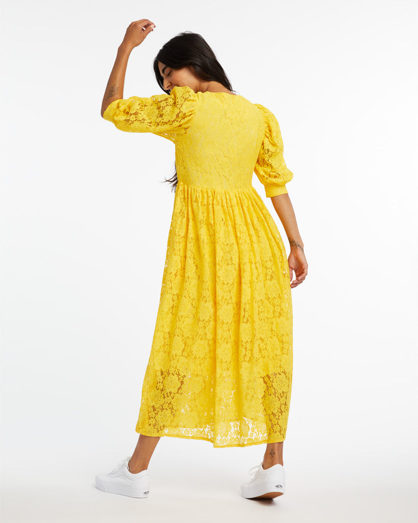 Back shot of woman in a midi length yellow lace dress with cropped puff sleeves.