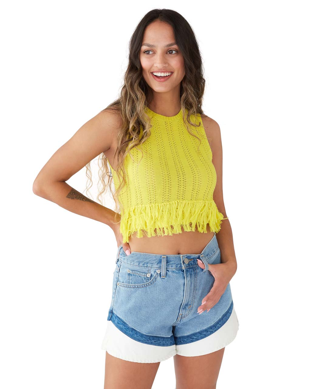 brunette model shown wearing a yellow fringe tank with blue jean shorts