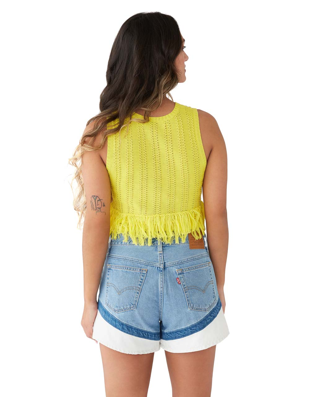 back view of brunette model shown wearing a yellow fringe tank paired with jean shorts