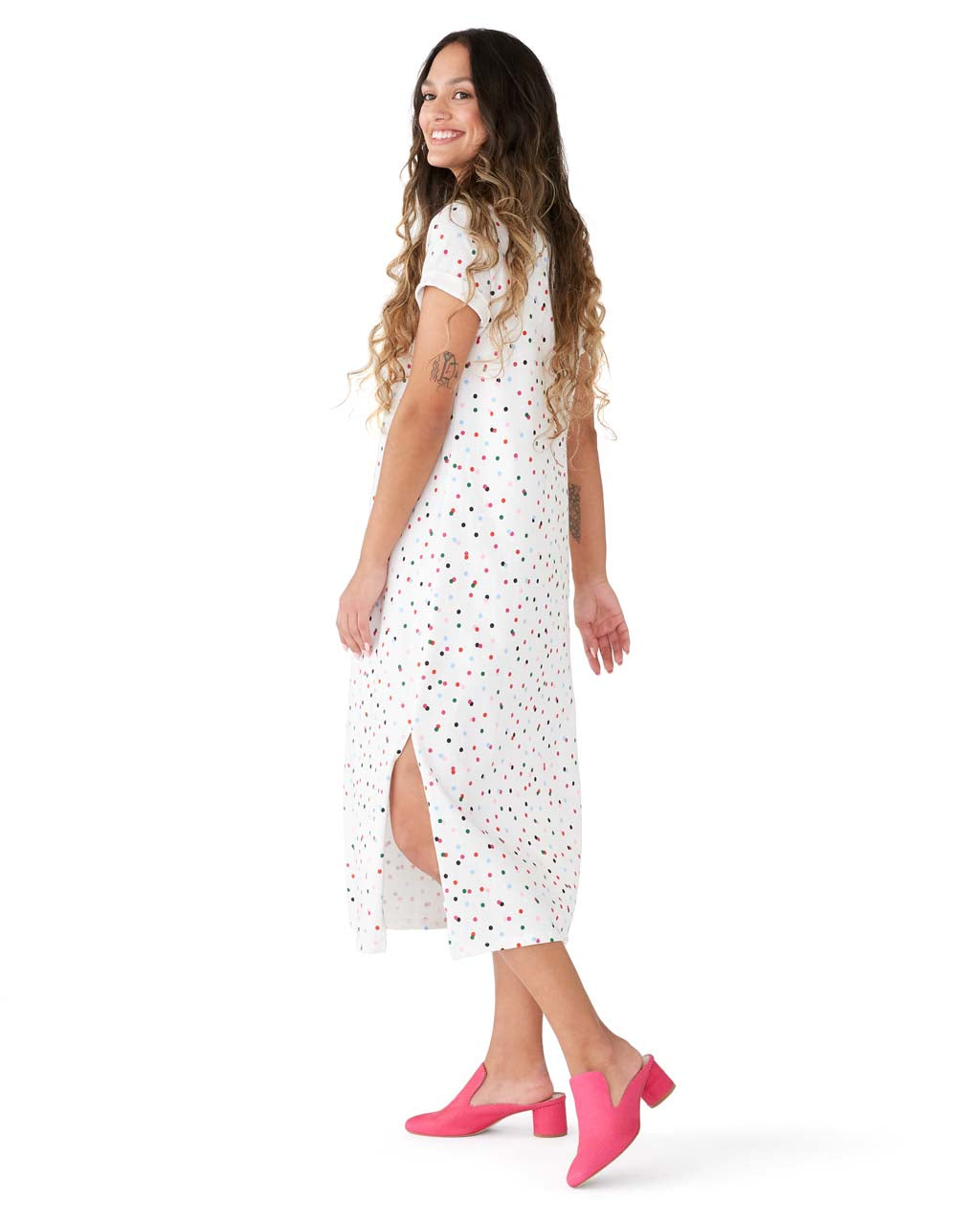 Woman in a white short sleeve midi length tshirt dress with multi-color polka dots.