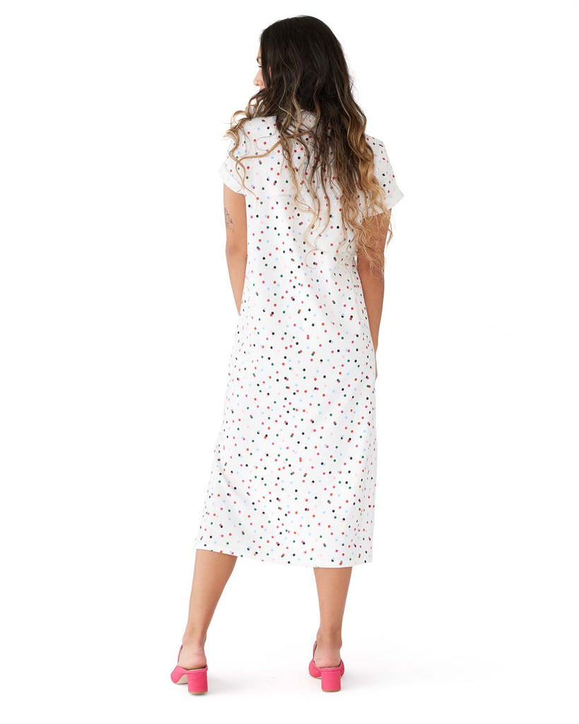 Back shot of a woman in a white short sleeve midi length tshirt dress with multi-color polka dots.