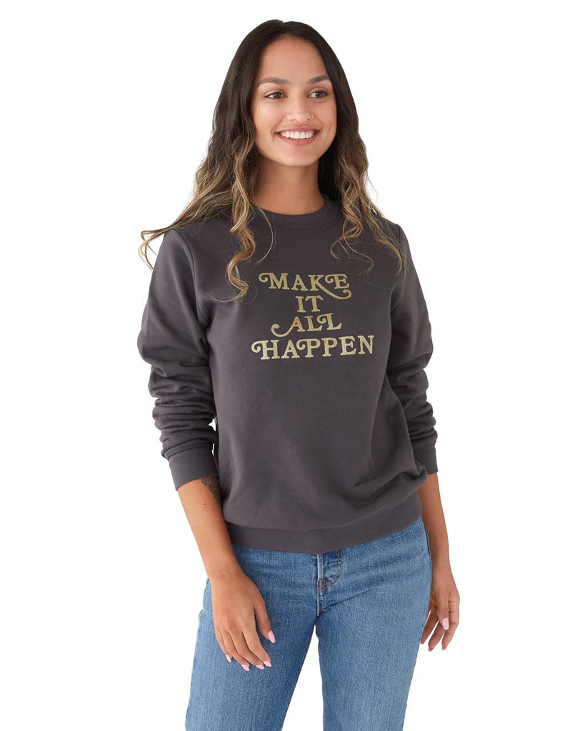 Woman in a long sleeve vintage black sweatshirt with a gold foil graphic Make It All Happen.