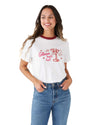 Woman in a white short sleeve ringer tee with a red collar and a pink graphic of a martini glass with the phrase Glass Half Full.