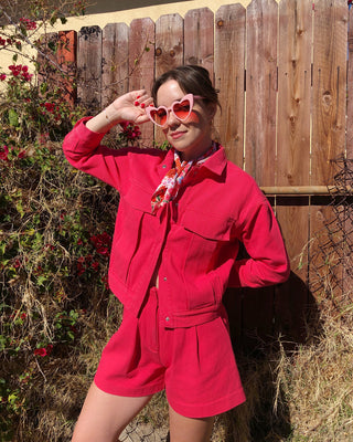 model wearing coral pink jacket with matching shorts and pink heart sunglasses