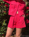 close up shot of model wearing coral pink jacket with matching shorts