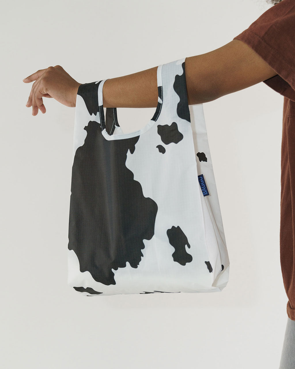 white and black cow print baby baggu shown on model arm