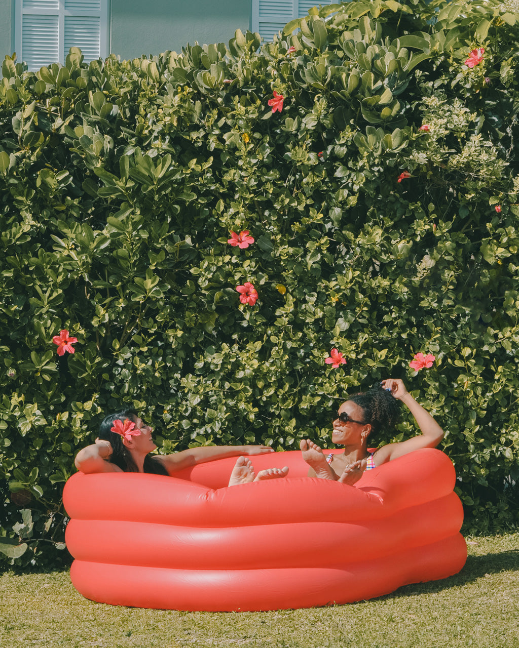 two woman in heart shaped inflatable pool on lawn in front of tall bush