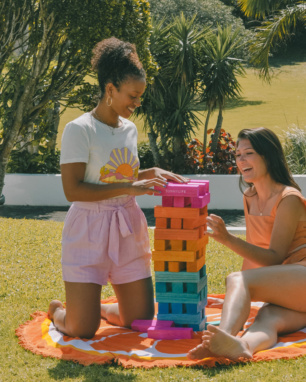 women playing with giant wooden jumbling tower on orange towel