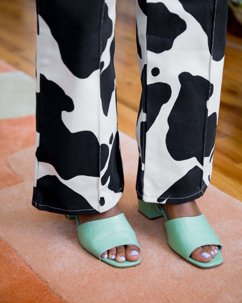 mint green sandals shown on model with cow print pants