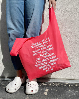 person wearing blue jeans and white croc slides holding pink baggu bag with white text