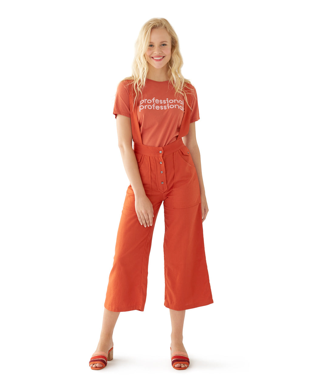 woman wearing rust colored wide leg overalls