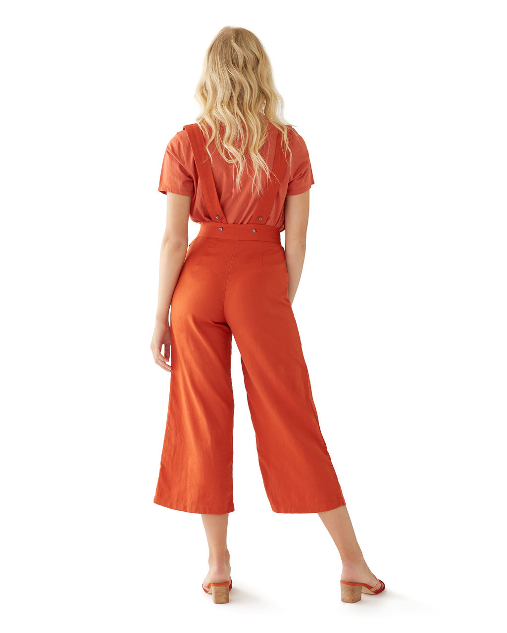 back view of woman wearing rust colored wide leg overalls