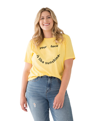 "woman in denim and a light yellow t-shirt that reads ""your face is like sunshine"""
