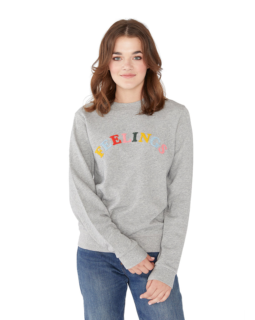 This sweatshirt comes in light grey with 'Feelings' colorfully embroidered on the front.