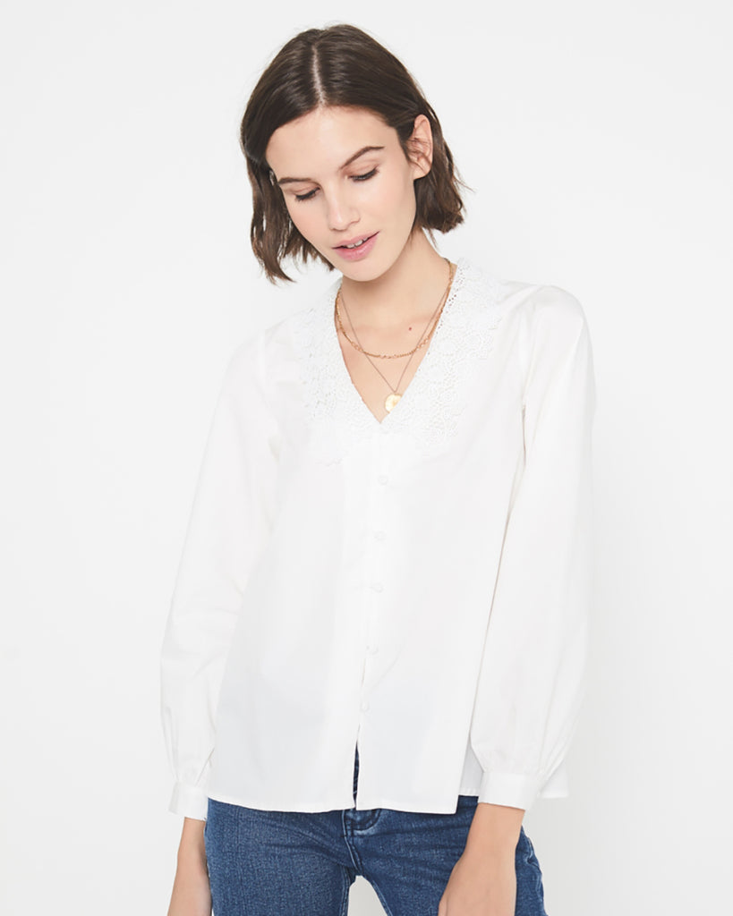 model in jeans wearing a white long sleeved blouse