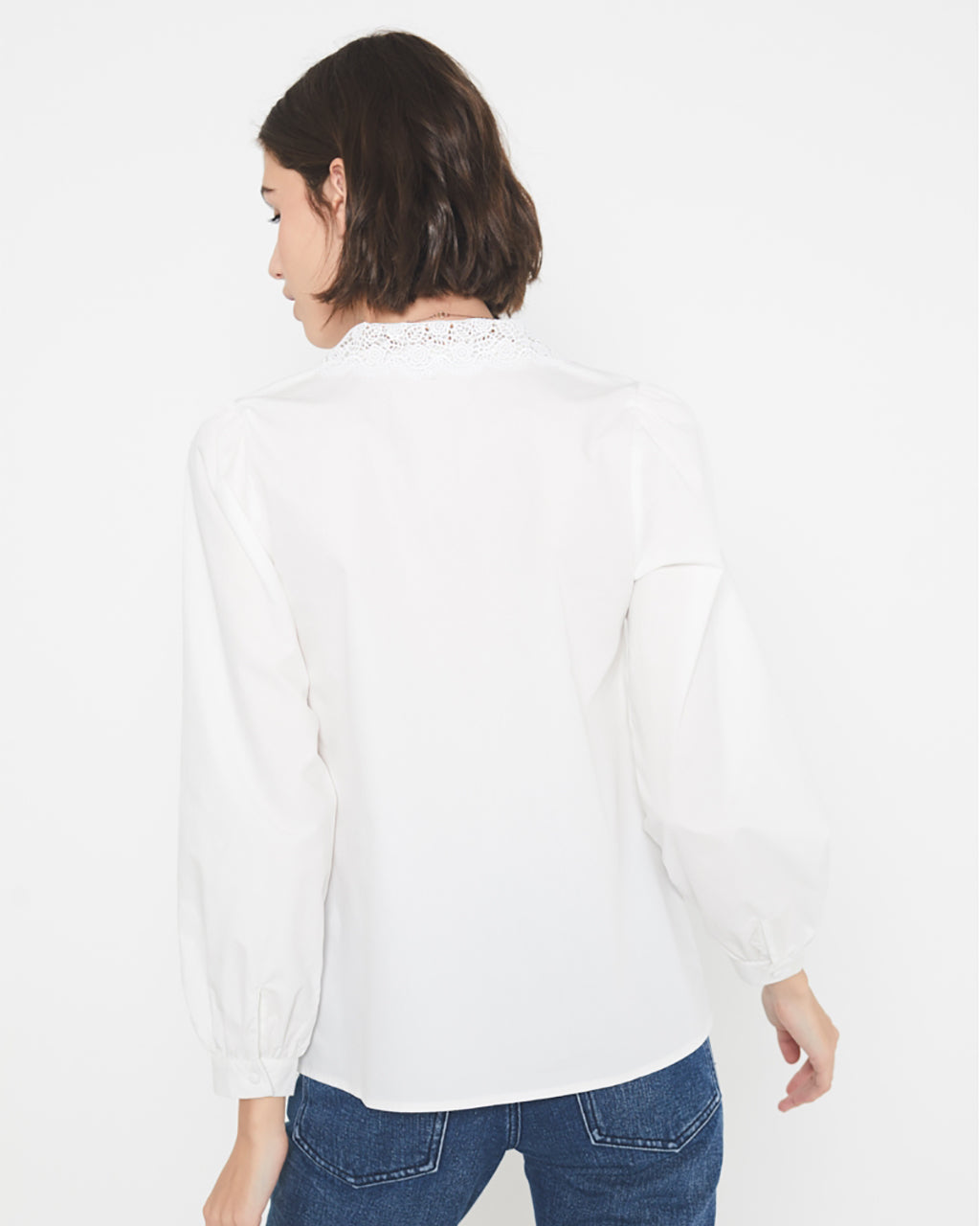 back view of model in long sleeved white blouse