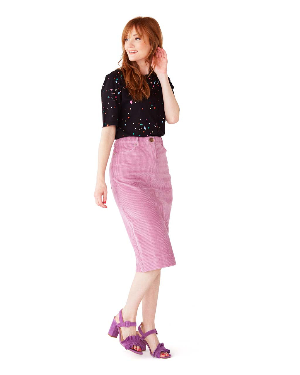 red headed model shown wearing lavender corduroy skit paired with a black tee and purple heels