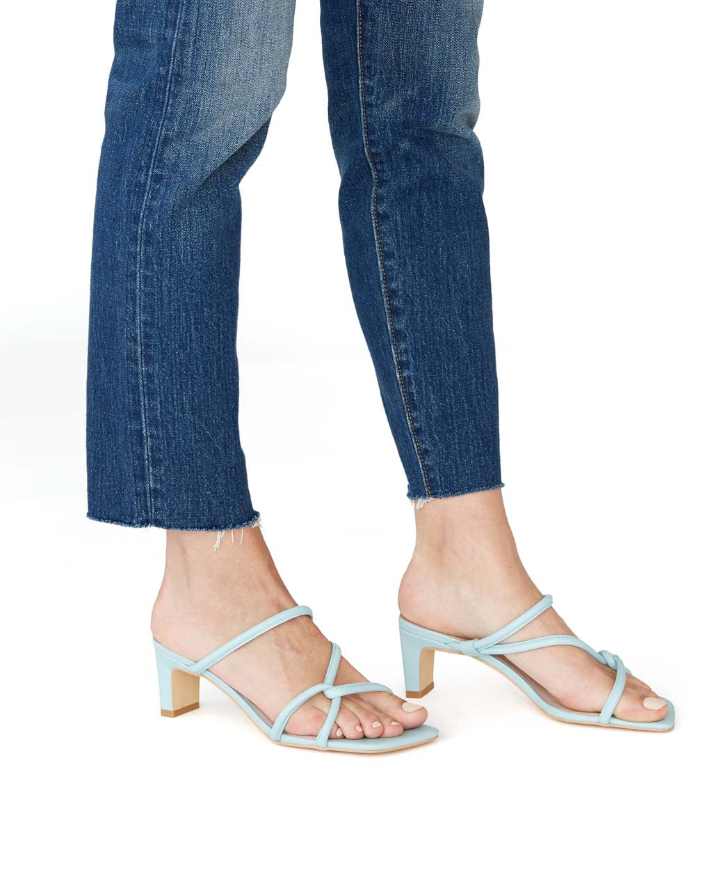 side view of model wearing baby blue backless sandals with heels