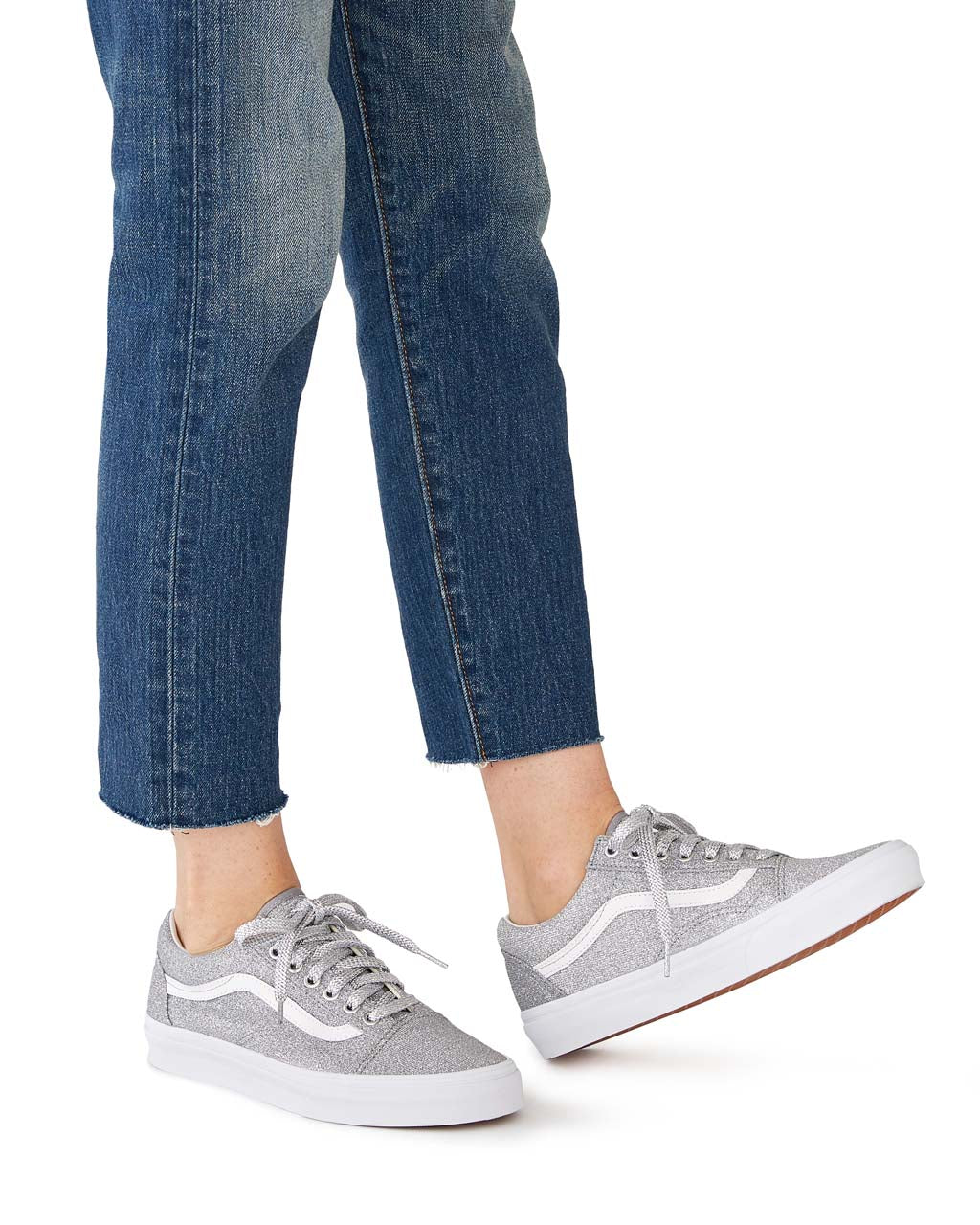 close up of woman wearing silver glitter Vans sneakers with jeans