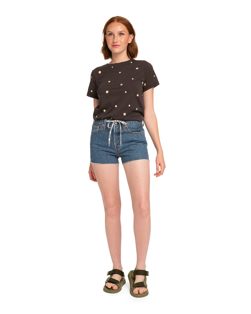Red headed woman in a grey daisy print tshirt, medium wash denim shorts with raw hem, logo printed drawstring, and black sandals.