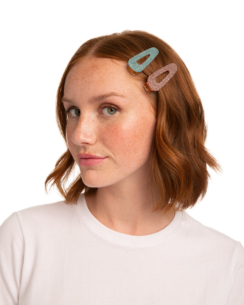 Model's hair kept back with pink and blue hair clips.
