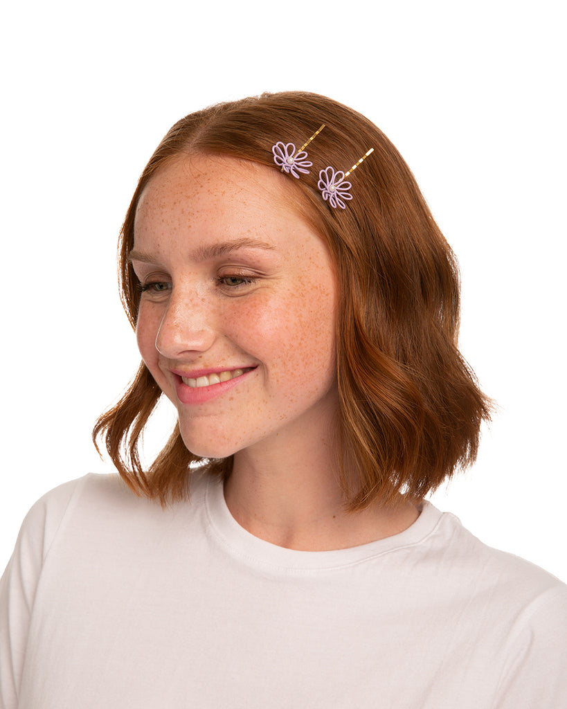 Red headed woman with two lilac and pearl floral barrettes pinned above her ear.