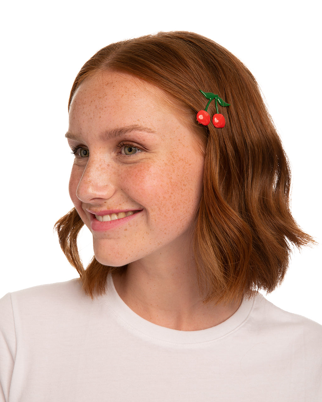Red headed woman with a red & green cherry barrette above her ear.