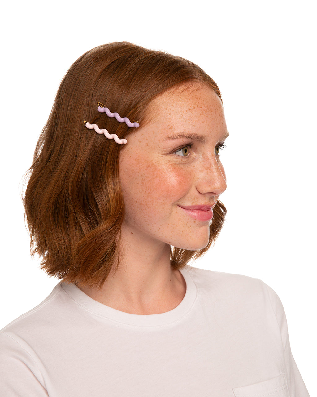 red headed model shown wearing a blush colored barrette and lilac colored barrette