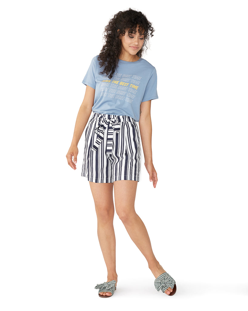 woman wearing a light blue t-shirt tucked into striped shorts