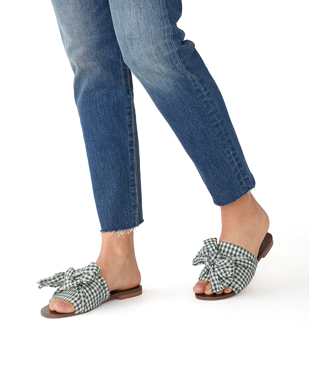 woman wearing jeans and backless sandals with green gingham bows