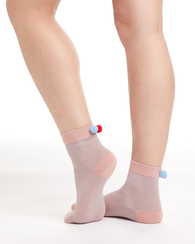 Pink tonal crew socks with red & blue pom poms on the back of the ankle.