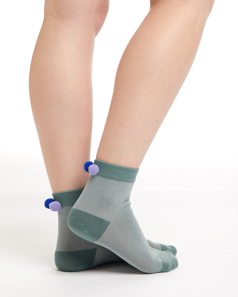 Green tonal crew socks with purple pom poms on the back ankle.