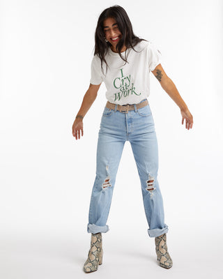 Woman in a graphic tee with high rise light wash distressed denim.