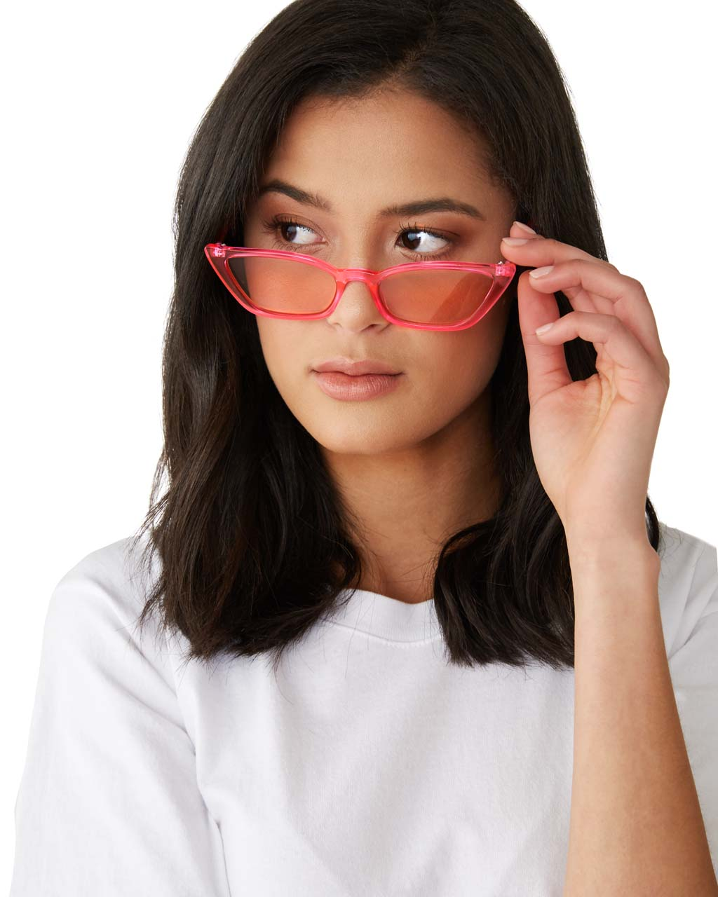 Brunette woman wearing transparent pink sunglasses with pink lenses and touching the side of the glasses.