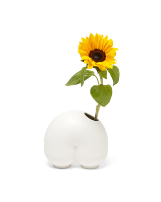 "white ceramic vase shaped like a ""n"" with a sunflower"