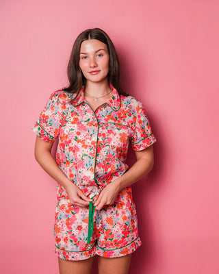 woman wearing bright floral pajama set with short sleeves and shorts