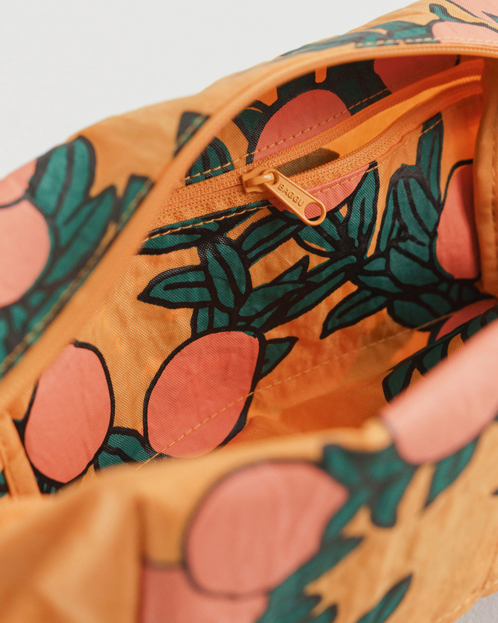 close up interior shot of dopp kit with handle in marigold with all over orange tree pattern
