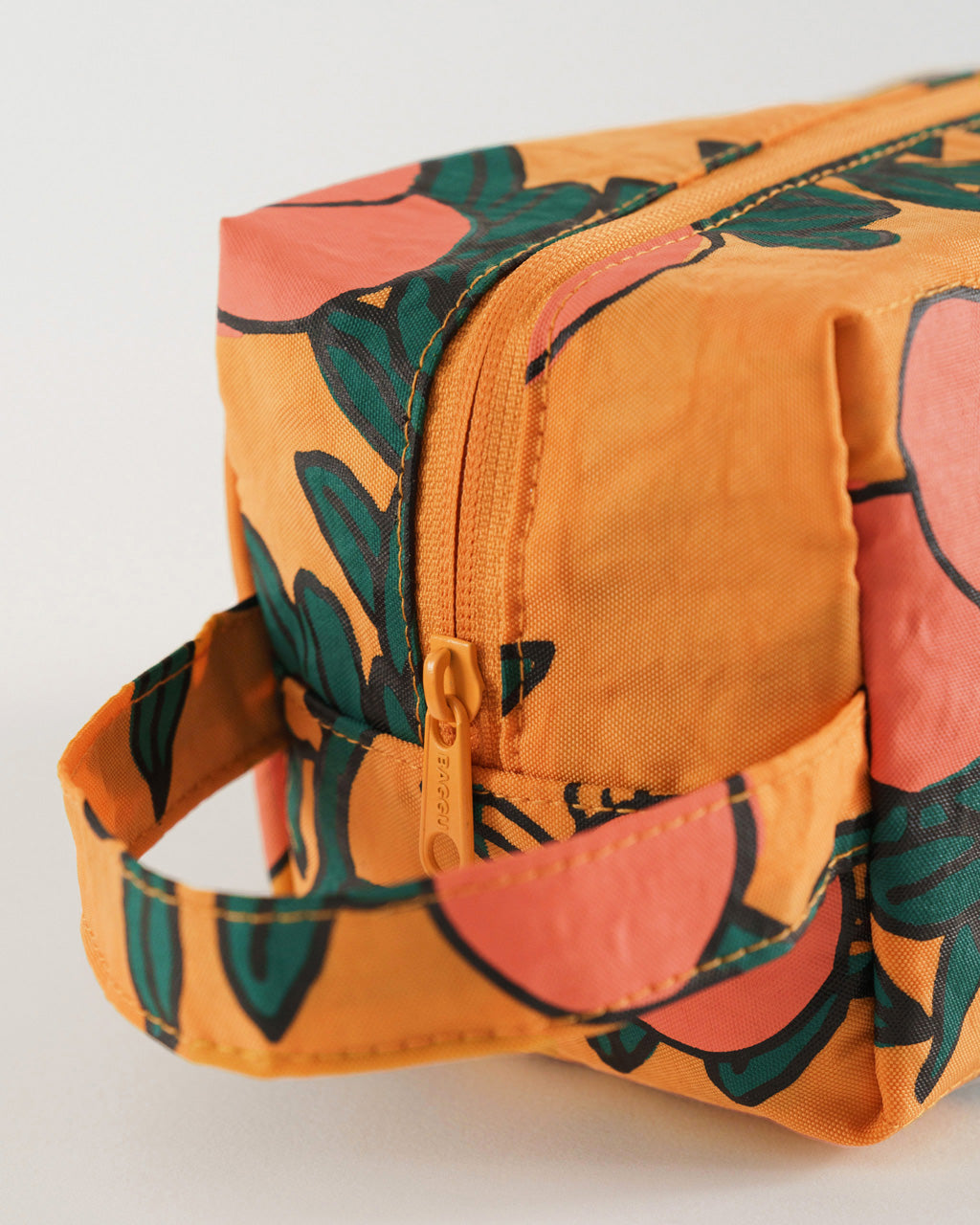 details shot of dopp kit with handle in marigold with all over orange tree pattern
