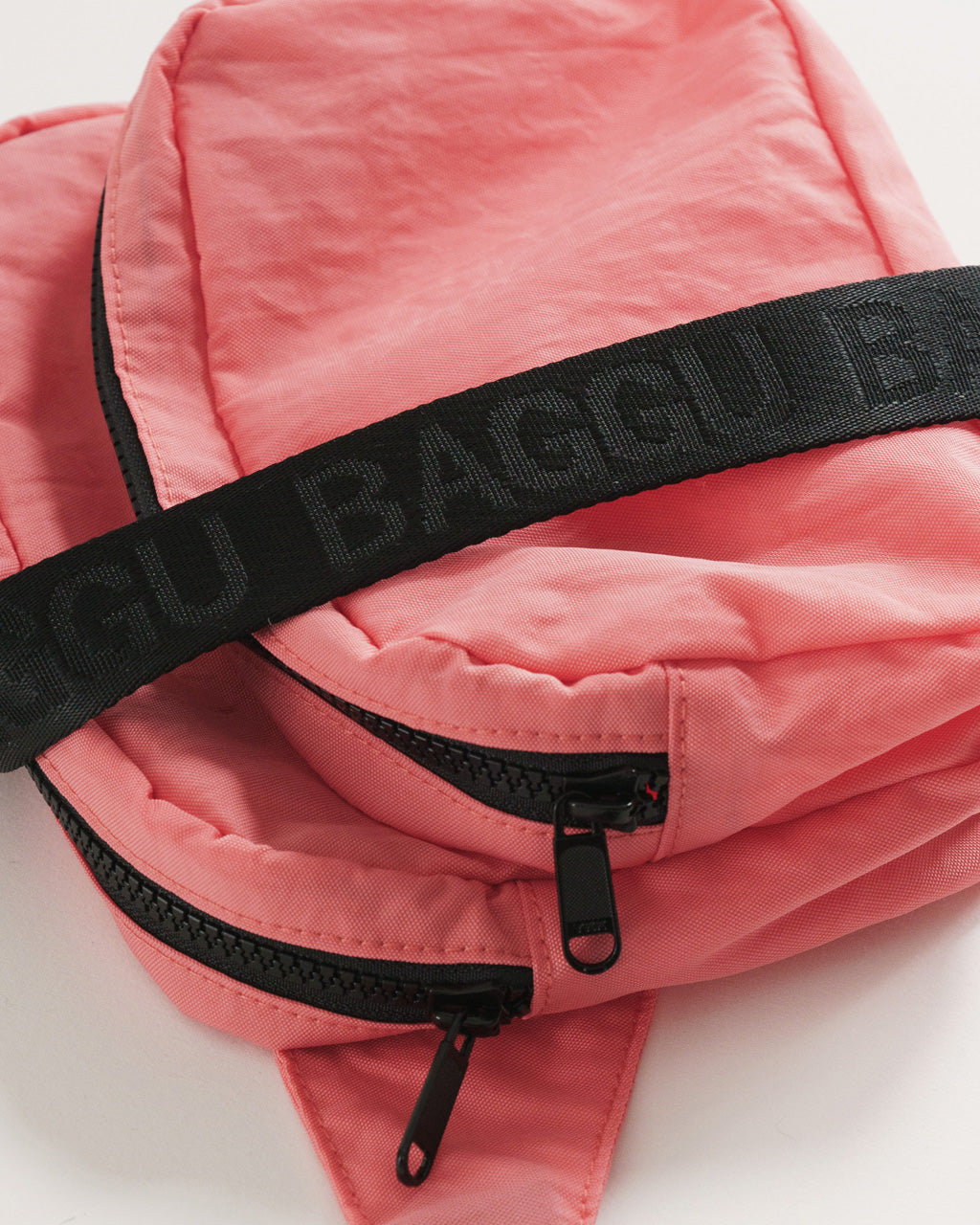 detail shot of nylon fanny pack in watermelon pink with black strap